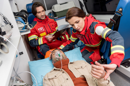 Paramedic holding oxygen mask on patient and checking pulse