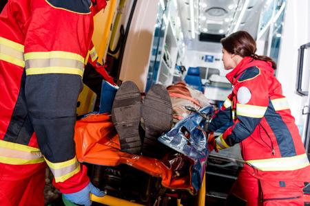 Photo pour Paramedics transportating patient on gurney in ambulance car - image libre de droit