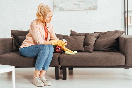 Foto de Senior woman in jeans cleaning sofa with spray and rag - Imagen libre de derechos