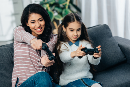 cute latin kid playing video game with attractive mother at home
