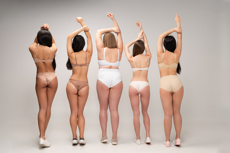 Photo for back view of five multiethnic women in underwear with raised hands, body positivity concept - Royalty Free Image