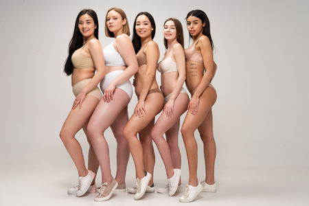 Photo pour five beautiful multiethnic woman in underwear and sneakers posing at camera and smiling, body positivity concept - image libre de droit