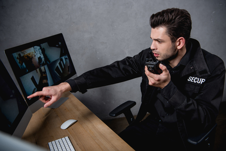Photo for guard in uniform talking on walkie-talkie and looking at computer monitor - Royalty Free Image