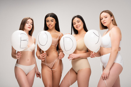 Photo for four attractive multiethnic women in lingerie holding air balloons with body lettering isolated on grey - Royalty Free Image