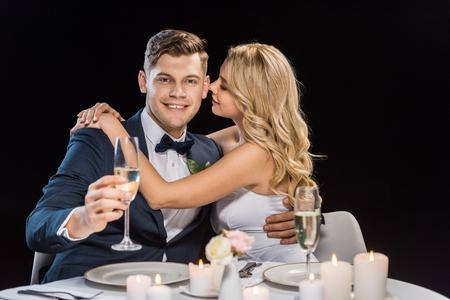 Foto de happy young bride embracing handsome groom with glass of champagne isolated on black - Imagen libre de derechos