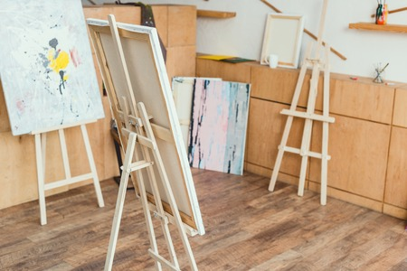 Photo for painting studio with wooden floor, cabinets, easels and paintings - Royalty Free Image