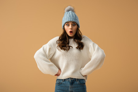 Photo pour Shocked curly young woman in blue hat standing with arms akimbo isolated on beige - image libre de droit