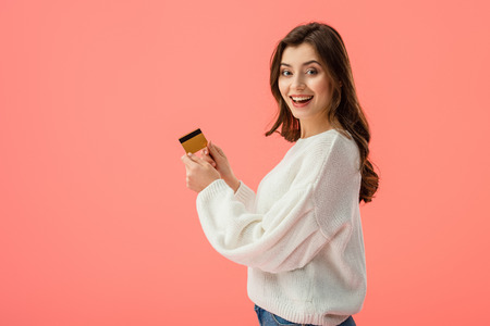 Photo pour happy brunette girl holding credit card isolated on pink - image libre de droit