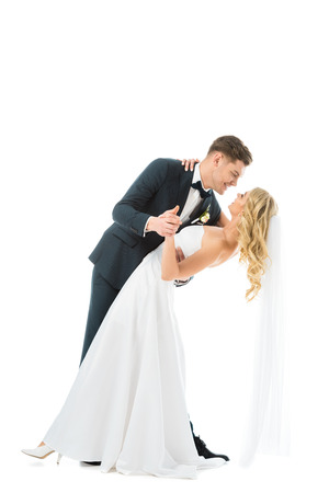 Photo pour handsome groom in elegant suit dancing with beautiful bride in wedding dress isolated on white - image libre de droit