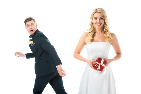 Foto de happy beautiful bride holding gift box, while tricky groom imitating running away isolated on white - Imagen libre de derechos