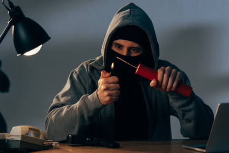Photo for Terrorist in mask and hoodie igniting dynamite in room - Royalty Free Image