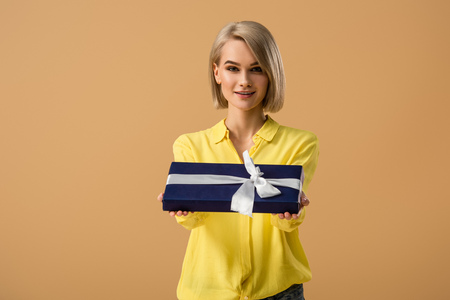 Foto de Pretty blonde young woman showing gift box with ribbon isolated on beige - Imagen libre de derechos