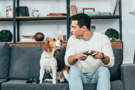 Smiling young man with gamepad sitting on sofa and looking at dog