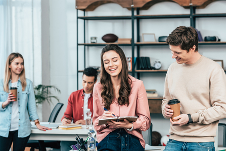 Photo pour Smiling young man with paper cup of coffee looking at girl with notebook - image libre de droit