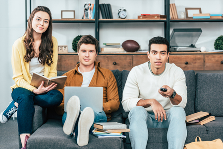 Photo pour Three multicultural students with notebooks and laptop studying and watching tv - image libre de droit