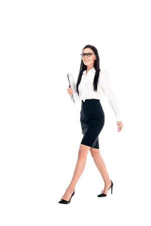 Photo pour Full length view of confident businesswoman in skirt walking isolated on white - image libre de droit