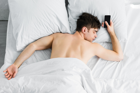 Photo pour handsome man sleeping under blanket near smartphone with blank screen on bad - image libre de droit