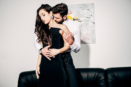 Foto de bearded man kissing and touching brunette woman in black dress - Imagen libre de derechos