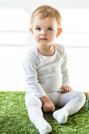 Foto de cute child with blonde hair sitting on green grass and looking away on white - Imagen libre de derechos