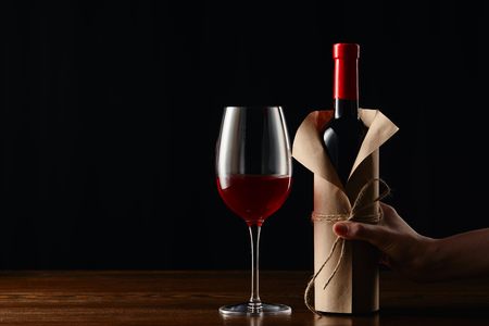 Foto de Partial view of woman holding wine bottle in paper wrapper - Imagen libre de derechos