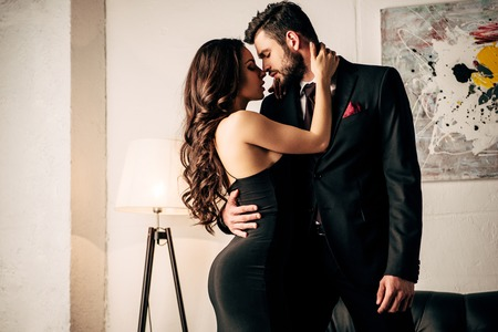 Photo pour attractive woman in black dress hugging with passionate man in suit - image libre de droit