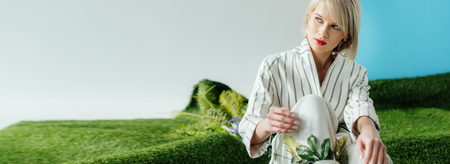 Foto de panoramic shot of beautiful stylish blonde girl sitting on artificial grass - Imagen libre de derechos