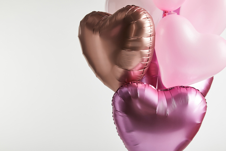 Foto de bundle of heart-shaped pink and golden balloons isolated on white with copy space - Imagen libre de derechos