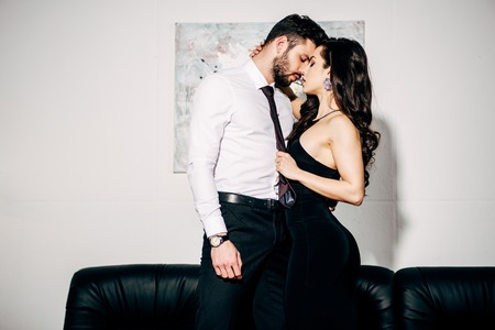Foto de beautiful girl in black dress kissing handsome man in suit - Imagen libre de derechos