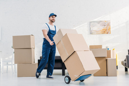 Photo pour mover in uniform transporting  cardboard boxes on hand truck in apartment - image libre de droit