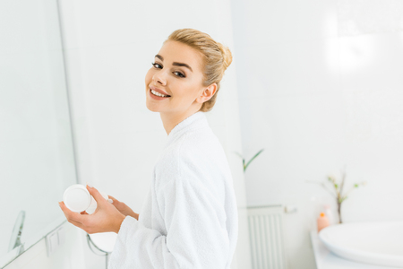 Photo pour smiling woman in white bathrobe holding cosmetic cream and looking at camera in bathroom - image libre de droit