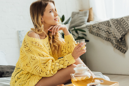 Photo pour beautiful young woman in knitted sweater sitting on bed, touching face and holding cup of tea - image libre de droit