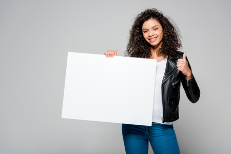 Photo pour cheerful african american young woman showing thumb up while holding blank placard  isolated on grey - image libre de droit