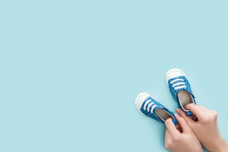 Foto de partial view of adult woman holding sneakers on blue background with copy space - Imagen libre de derechos