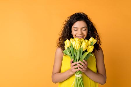 Foto de happy curly african american woman smelling yellow tulips isolated on orange - Imagen libre de derechos