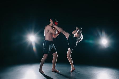 Foto de strong mma fighter kicking another sportsman in head during fight - Imagen libre de derechos