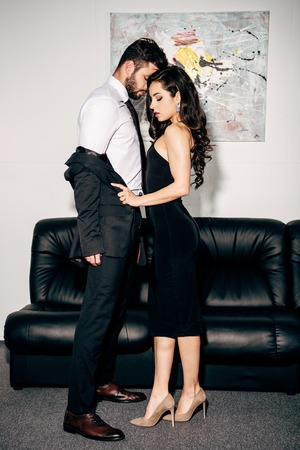 Foto de beautiful woman in black dress undressing man in suit near sofa - Imagen libre de derechos