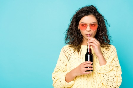 Photo pour curly african american girl in sunglasses holding bottle with straw and drinking soda isolated on blue - image libre de droit