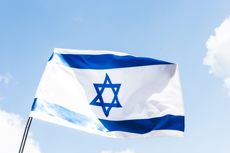 Photo pour low angle view of national israel flag with blue star of david against sky - image libre de droit