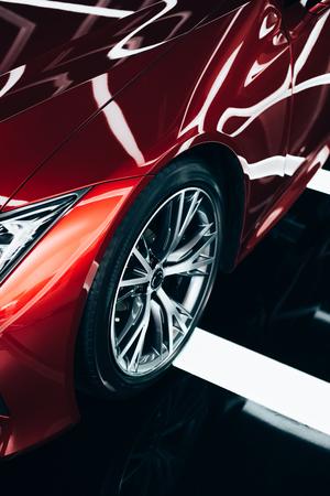 Foto de new shiny red automobile with metallic wheel in car showroom - Imagen libre de derechos