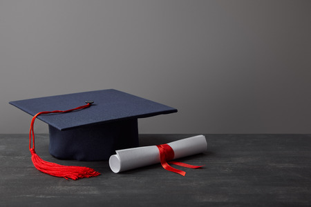 Photo pour Diploma and academic cap with red tassel on dark surface on grey - image libre de droit
