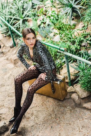 Dreamy sexy woman in black pantyhose sitting on suitcase in botanical garden