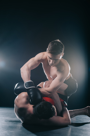 Photo pour shirtless strong mma fighter in boxing gloves clinching opponent on floor - image libre de droit