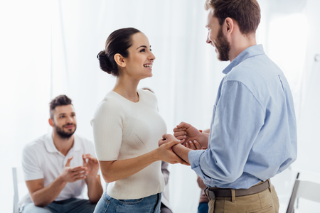Photo pour beautiful smiling woman holding hands with man during group therapy session - image libre de droit