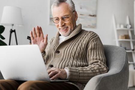 Photo for cheerful senior man in glasses waving hand while having video call - Royalty Free Image