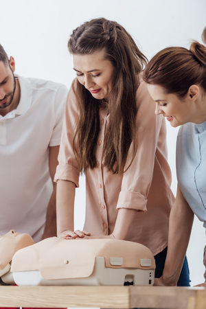 Photo for beautiful woman performing chest compression on dummy during cpr training class - Royalty Free Image