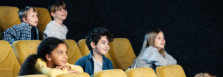 Foto de panoramic shot of multicultural friends spending time in cinema together - Imagen libre de derechos