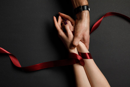Photo for cropped view of man holding female hands in red satin ribbon on black background - Royalty Free Image