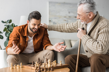 Photo for retired father in glasses putting hand on shoulder of happy son while playing chess - Royalty Free Image