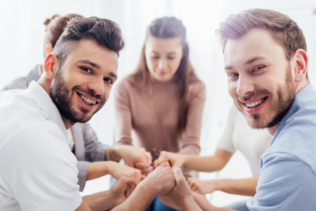 Photo pour group of people sitting, smiling and stacking hands during therapy session - image libre de droit