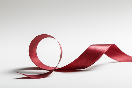 Photo for shiny silk wavy burgundy ribbon on grey background - Royalty Free Image